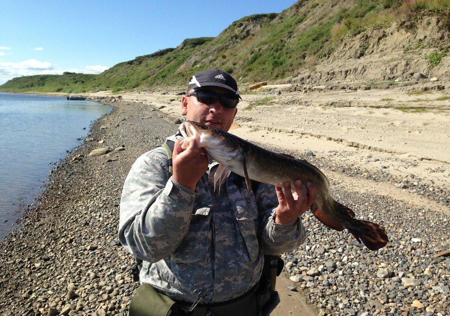 Парень на берегу с рыбой в руках