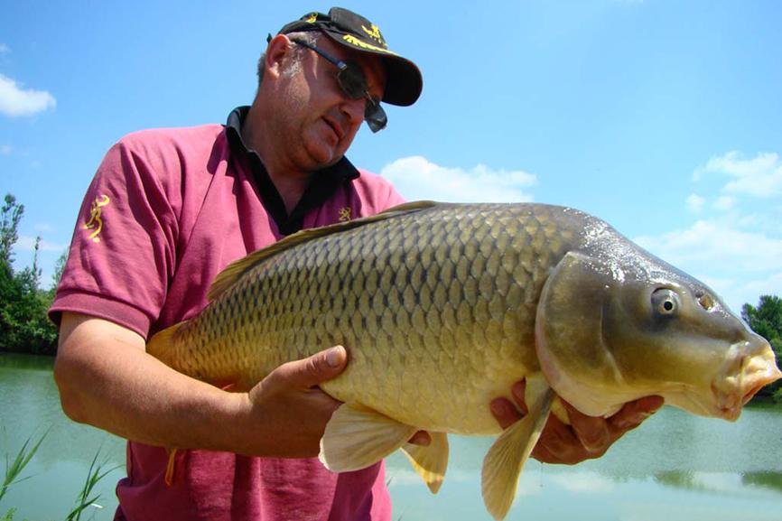 Рыбак в кепки с пойманным сазанчиком золотого цвета