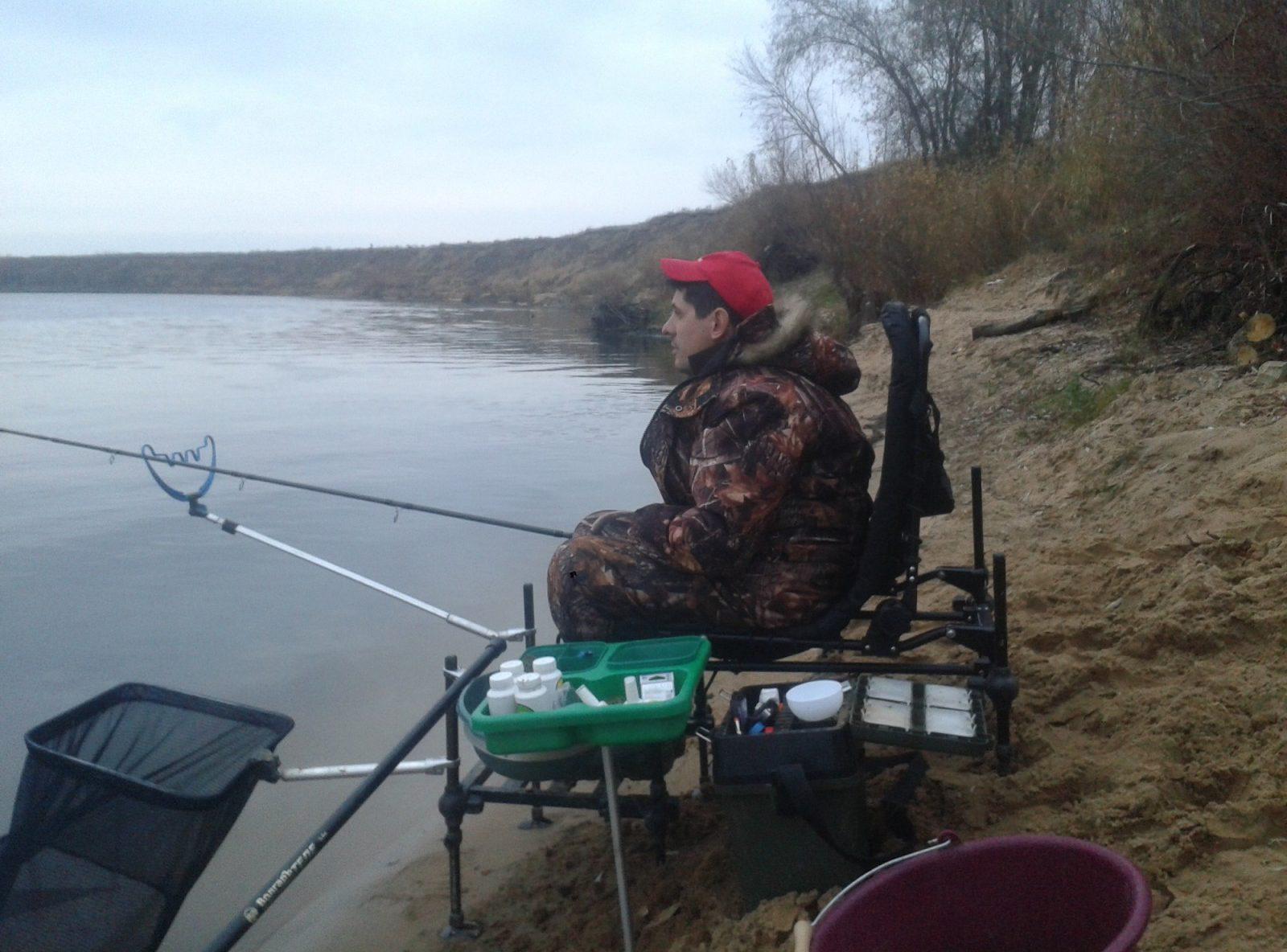 Рыбак с удочкой в кресле на берегу реки
