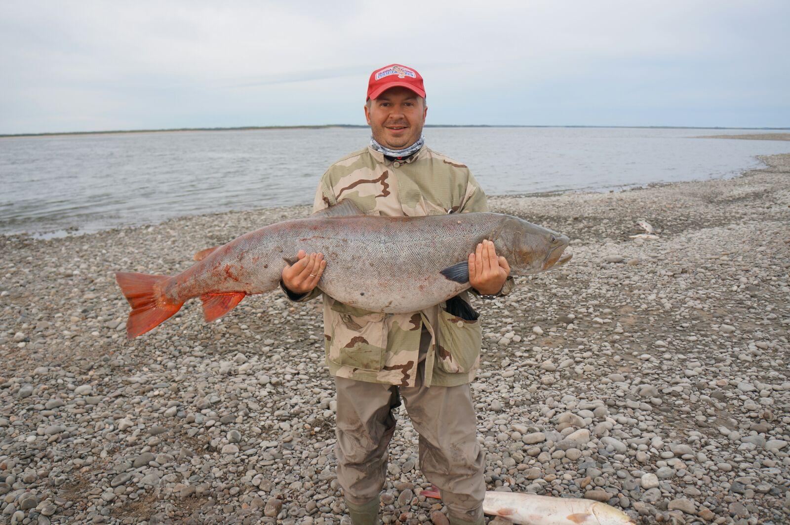 Мужик в красной кепке с трофейной рыбиной