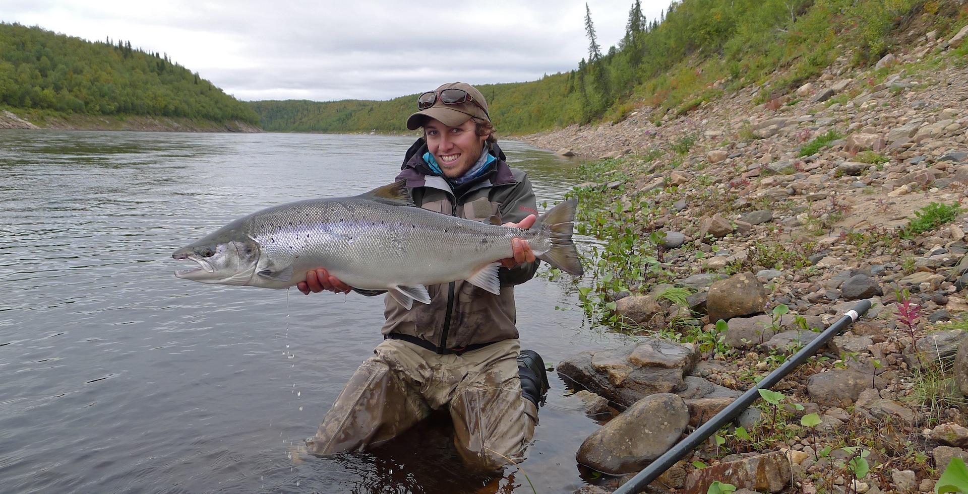 Довольный рыбак с пойманной рыбой