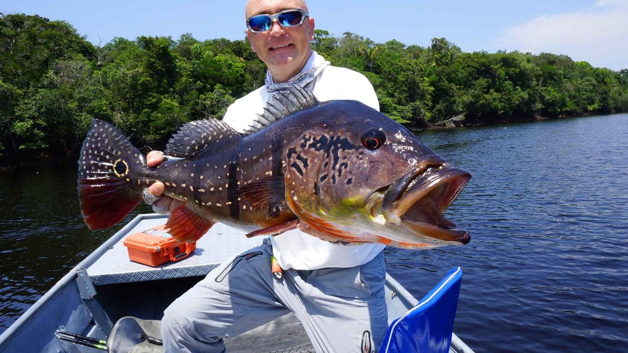 Мужик в лодке с очень красивой рыбой