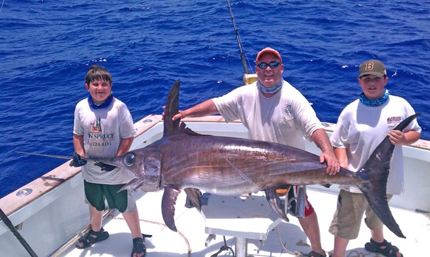 Три рыбака с огромной рыбой