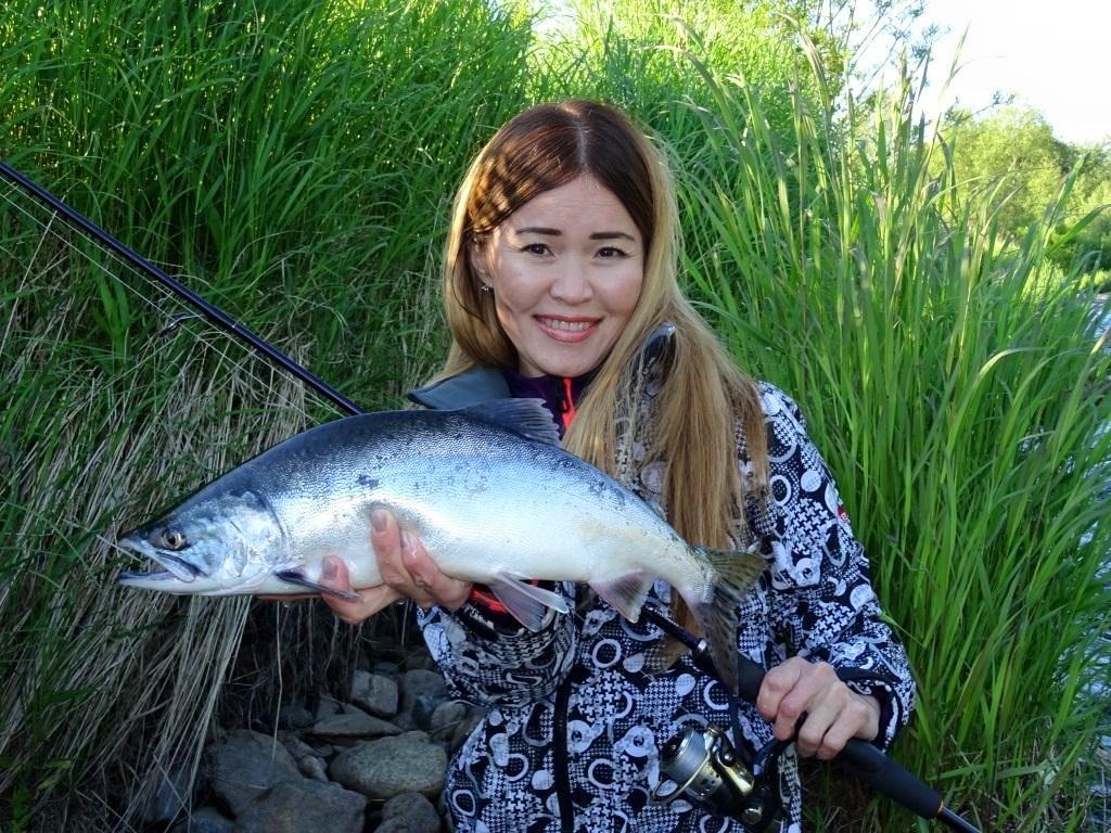 Девушка с пойманной рыбой и удочкой в руках