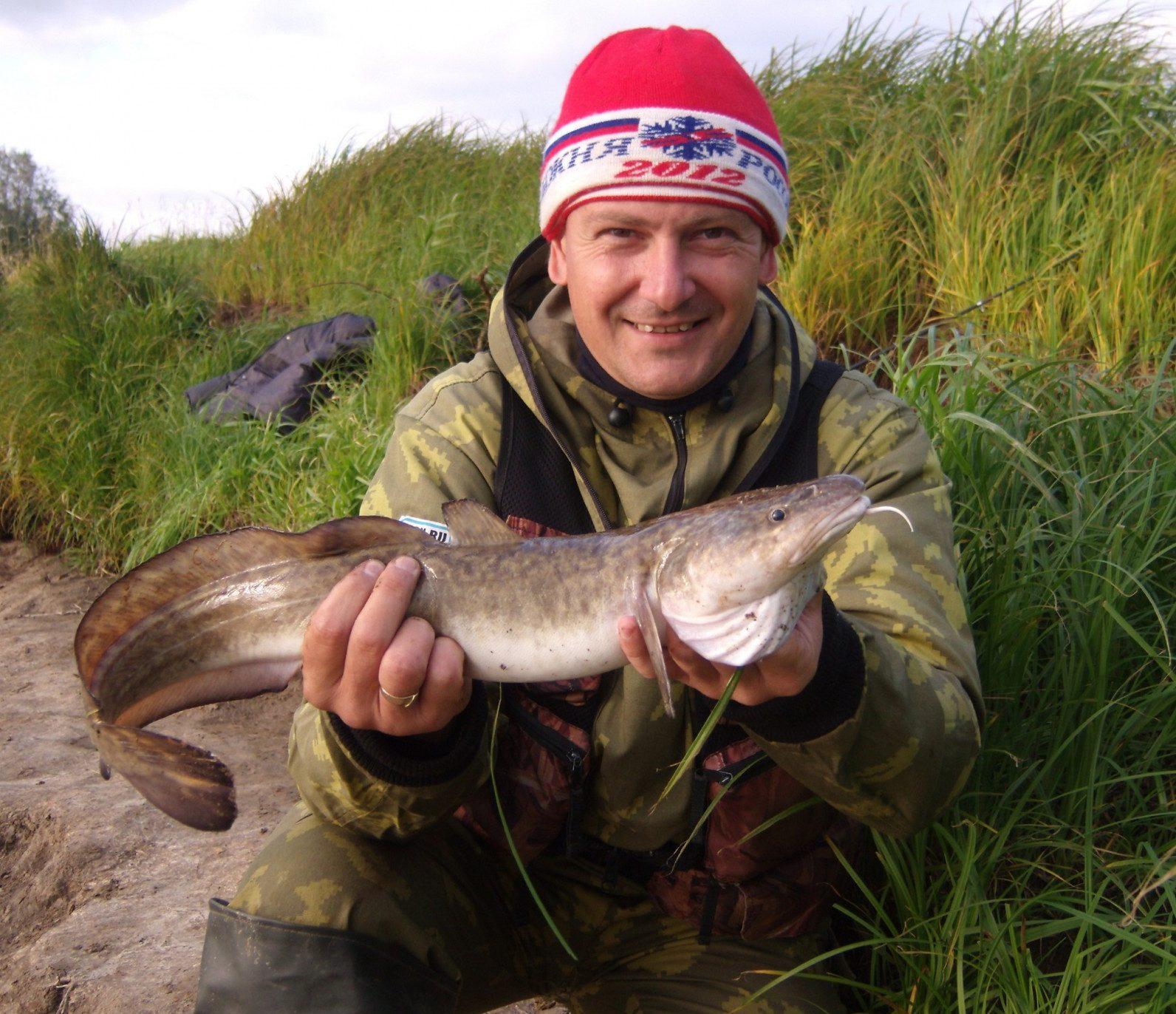 Довольный рыбак в красной шапке