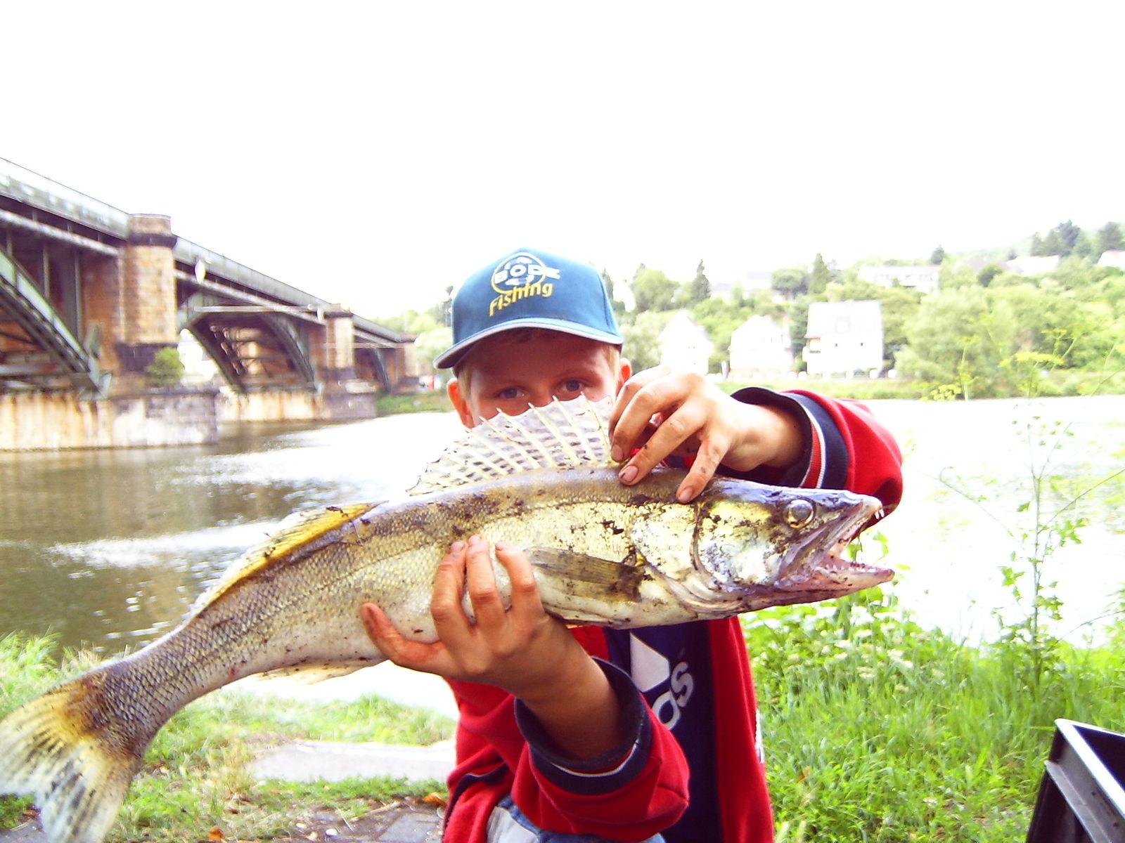 Мальчик с пойманной рыбай в руках