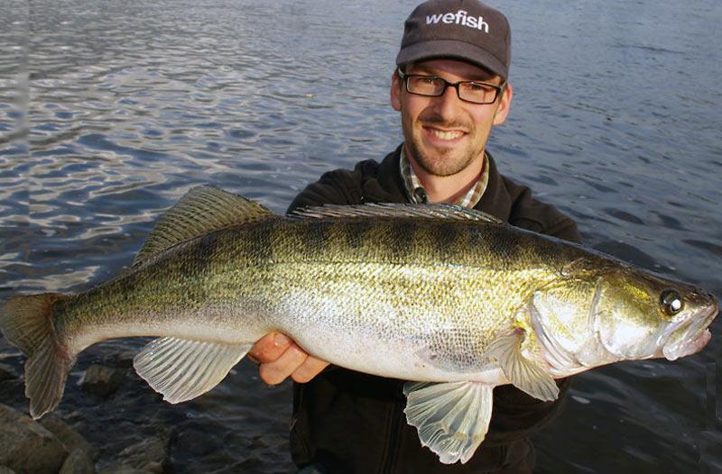 Рыбак с крупной рыбой в руках
