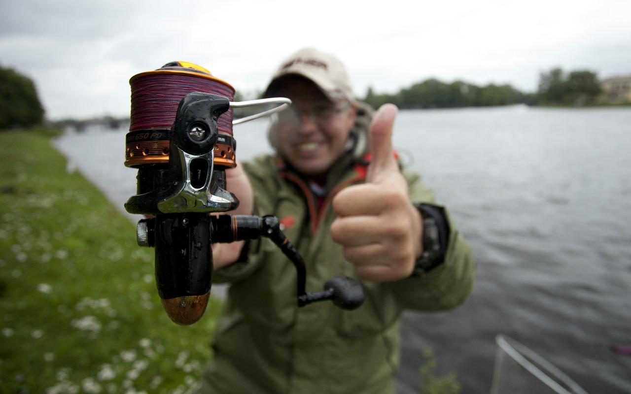 Довольный рыбак своей катушкой