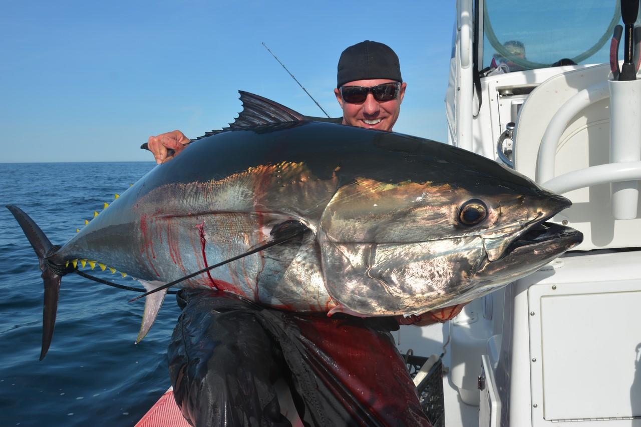 Парень в лодке с огромной рыбой в руках
