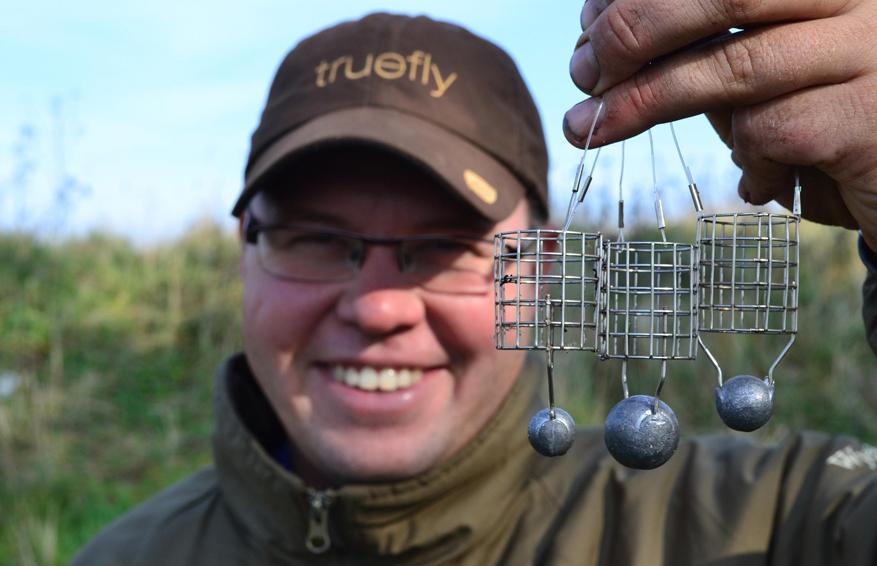 Довольный рыбак с кормушками в руках