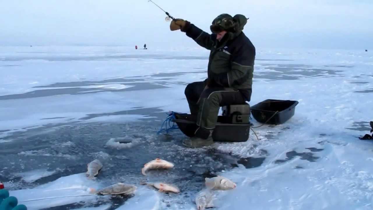 Мужик на льду с удочкой в руках