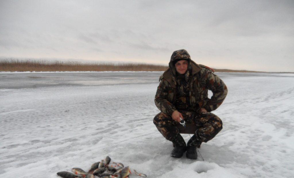 Рыбак на зимней рыбалки с кучей рыбы